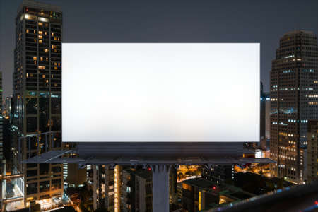 Blank white road billboard with Bangkok cityscape background at night time. Street advertising poster, mock up, 3D rendering. Front view. The concept of marketing communication to promote idea. Stock Photo