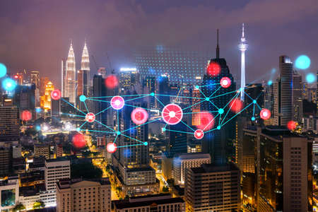 Abstract technology icons, night aerial panoramic cityscape of Kuala Lumpur, Malaysia, Asia. The concept of innovative approach to optimize international business process. Double exposure. Banque d'images