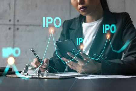 Businesswoman taking notes and IPO hologram. Double exposure. Business technology initial primary offering solution concept.