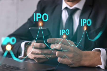 Businessman search and analyze using on-line app on phone. IPO theme hologram. Stock Photo