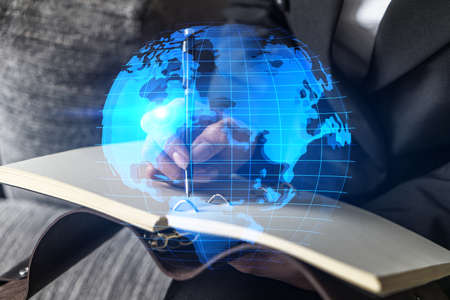 Planet earth map hologram and a woman taking notes. International network concept. Multiexposure.