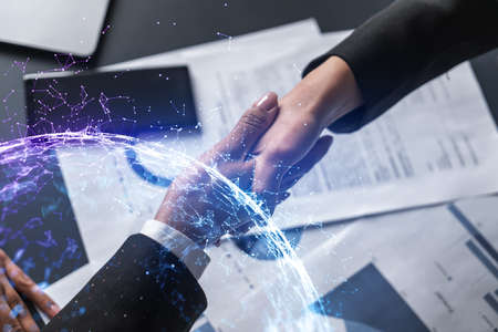 Double exposure of two businesspeople handshake and abstract technology hologram drawing background. Concept of high tech business. Formal wear. Stock fotó