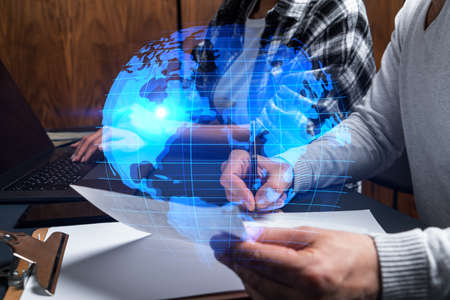 Man and woman working together on international business project. Blue infographic hologram of planet earth. World map. Multiexposure.