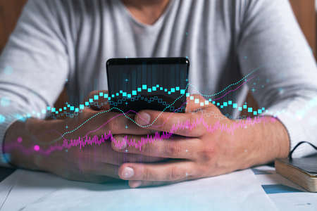 Man using phone. Hands typing smartphone. Double exposure with forex graph hologram. Close up. Financial chart and analysis concept. On-line trading and investment.