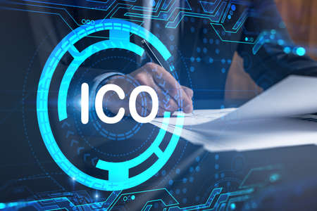 Businessman in suit signs white papper. Double exposure with ICO icon hologram. Man signing contract agreement. Blockchain market analysis and investment concept.