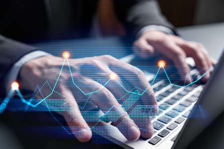 Businessman trading on-line, typing laptop background and financial graph hologram.