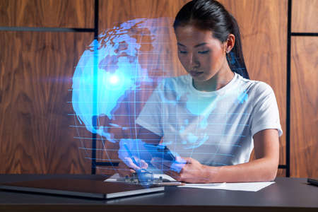 Woman takes notes with smartphone. world map and people network concept hologram. Multiexposure.