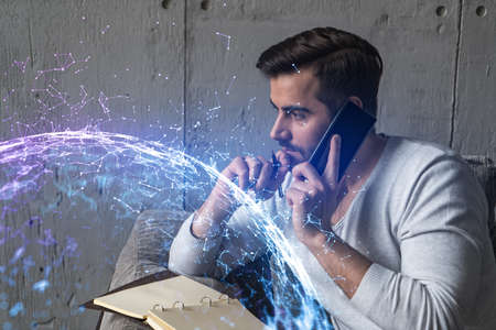 Handsome manager in casual wears, speaking phone, taking notes at office try to solve IT challenge from client. Double exposure. The concept of abstract technology.