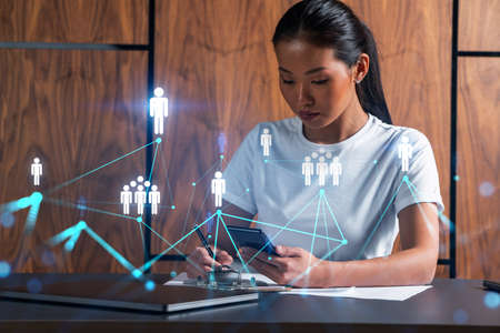 Woman takes notes with smartphone. Social media and people network concept hologram. Multiexposure.