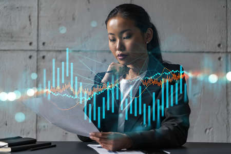 Asian businesswoman dream of success. forex stock market graph drawing hologram. Double exposure. Stock Photo