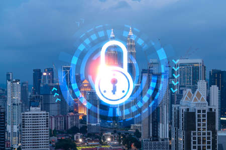 Glowing Padlock hologram, night panoramic city view of Kuala Lumpur, Malaysia, Asia. The concept of cyber security to protect KL companies. Double exposure.