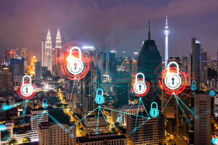 Glowing Padlock hologram, night panoramic city view of Kuala Lumpur, Malaysia, Asia. The concept of cyber security to protect KL companies. Double exposure. Фото со стока