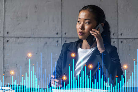 Businesswoman speaks phone and stock market financial graph hologram. Double exposure. Company statistics study concept.