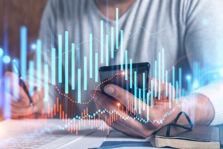 Double exposure of man signing contract with phone and forex graph hologram. Concept of financial market, stock exchange, investment in bonds.