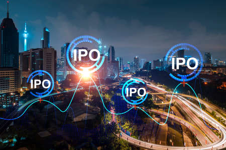 Initial public offering hologram, night panoramic city view Kuala Lumpur. KL is the financial center for multinational corporations in Malaysia, Asia. The concept of boosting growth by IPO process.
