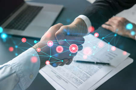 Double exposure of two businesspeople handshake and abstract technology hologram drawing background. Concept of high tech business. Formal wear. Banco de Imagens