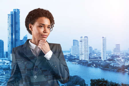 Attractive black African American business woman in suit with hand on chin thinking how to succeed, new career opportunities, MBA. Bangkok on background. Double exposure.