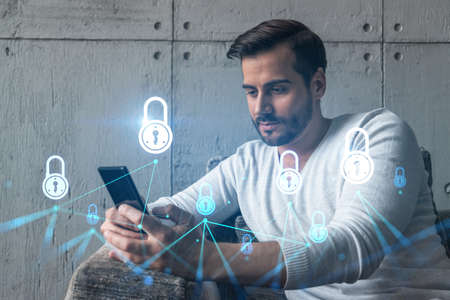 A man typing mobile phone. Double exposure. Lock icon hologram. Protection of data information concept.
