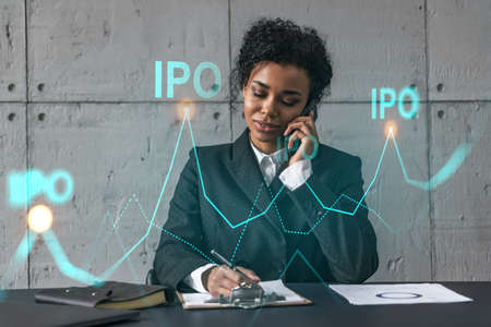 Businesswoman speaks phone and ipo icon hologram. Double exposure. Initial primary offering invest concept.
