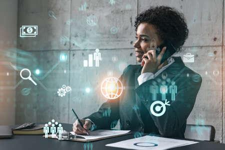 Businesswoman speaks phone andbusiness theme hologram. Double exposure. Standard-Bild