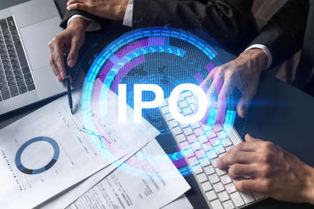 Two business people working together on white paper to release and present IPO project to investors. Initial primary offering hologram. Double exposure. Stock Photo