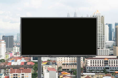 Blank black road billboard with Kuala Lumpur cityscape background at day time. Street advertising poster, mock up, 3D rendering. Front view. Concept of marketing to promote or sell services or ideas.