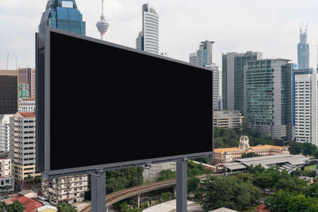 Blank black road billboard with Kuala Lumpur cityscape background at day time. Street advertising poster, mock up, 3D rendering. Side view. The concept of marketing communication.