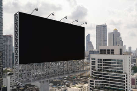 Blank black road billboard with Bangkok cityscape background at day time. Street advertising poster, mock up, 3D rendering. Side view. The concept of marketing communication to promote or sell idea.