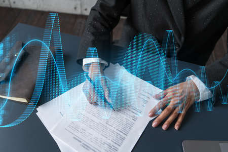 Woman signs agreement. Financial market chart and graph hologram. Double exposure . Business Analysis concept.