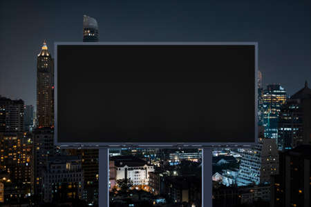 Blank black road billboard with Bangkok cityscape background at night time. Street advertising poster, mock up, 3D rendering. Front view. The concept of marketing communication to sell idea.