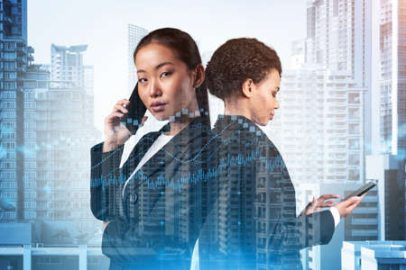 Two young astonishing businesswoman in suits working on forecasting trading corporate strategy at fund. Forex chart. Bangkok on background. Double exposure.