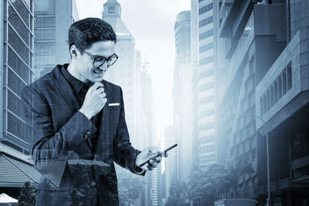 Young handsome businessman in suit and glasses using phone and thinking how to tackle the problem, new career opportunities, MBA. Singapore on background. Double exposure. 免版税图像