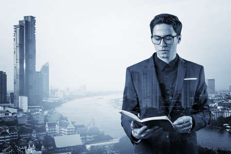 Young handsome businessman in suit and glasses thinking how to tackle the problem, new career opportunities, MBA assignment. Bangkok on background. Double exposure.