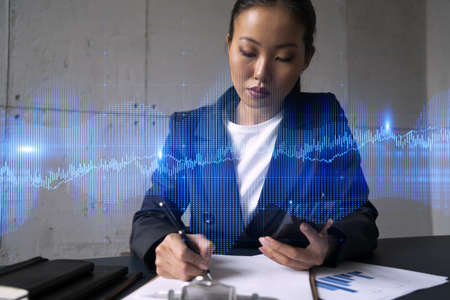 Businesswoman taking notes and forex graph hologram. Double exposure. Business technology online trading stock market solution concept. Banque d'images