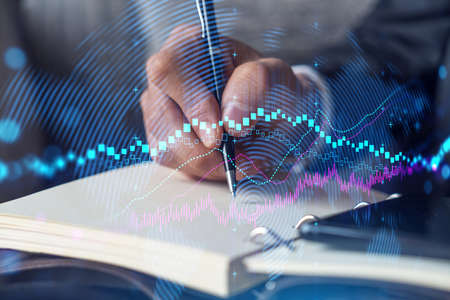 Businessman in suit taking notes. Multiexposure with forex graph hologram. Man writing down important information in his business diary. Financial trading concept. Banque d'images