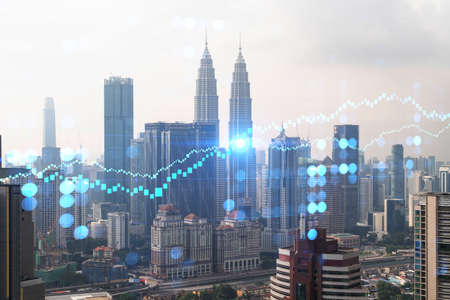 Forex and stock market chart hologram over panorama city view of Kuala Lumpur. KL is the financial center in Malaysia, Asia. The concept of international trading. Double exposure.