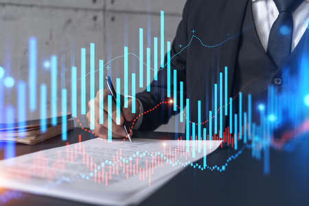 Businessman in suit signs contract. Double exposure with forex graph hologram. Man signing brokerage agreement. Financial market analysis and investment concept.
