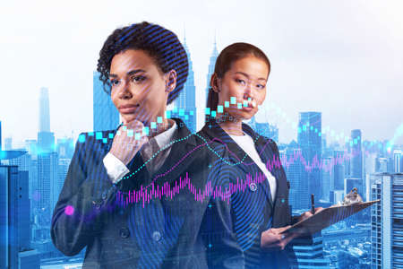 Two young attractive businesswoman in suits pondering about new venture capital and hi-tech start up and try to forecast risks and estimate prospective earning growth. Hologram chart on Kuala Lumpur.
