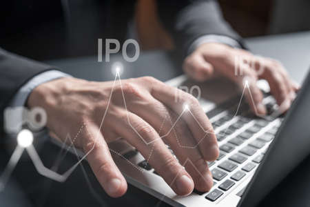 Businessman search on-line for investment opportunities, typing laptop background and ipo icon hologram.