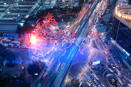 World planet Earth map hologram on aerial view of road, busy urban traffic highway at night. Junction network of transportation infrastructure. The concept of success in logistics business.