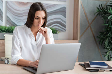 Office manager woman wearing white shirt, sitting to table with laptop and notebooks. Concentrated office worker looking at the screen in big light office room. Concept of work