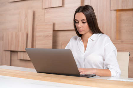 Office manager woman wearing white shirt, sitting to table with laptop on background of wooden office wall, side view. Concentrated office worker looking at the screen. Concept of work