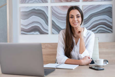 Office manager woman wearing white shirt, smiling sitting to table with laptop and cup of coffee, looking at the camera. Happy office worker in big light office room. Concept of work