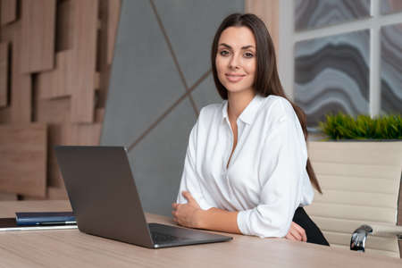 Office manager woman wearing white shirt, smiling sitting to table with laptop, side view, looking at the camera. Happy office worker in big light office room. Concept of work