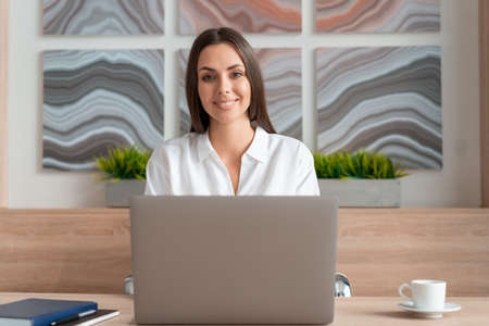 Office manager woman wearing white shirt, smiling sitting to table with laptop, looking at the camera. Happy office worker in big light office room. Concept of work