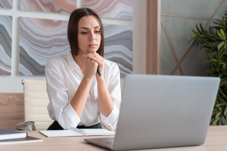 Office manager woman wearing white shirt, sitting to table with laptop thinking looking at the screen, holding a pen. Concentrated office worker in big light office room. Concept of work 免版税图像