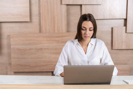 Office manager woman wearing white shirt, sitting to table with laptop on background of wooden office wall. Concentrated office worker looking at the screen. Concept of work