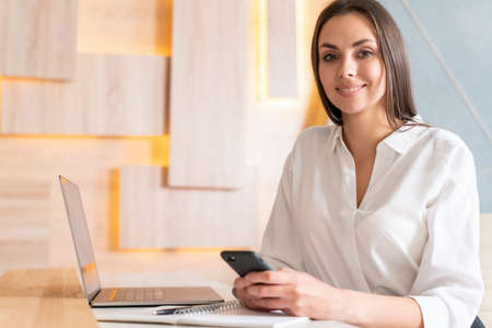 Office manager woman in white shirt, sitting to table with phone in hands and notebook with laptop on the table. Smiling office worker looking at the camera in big light office room. Concept of work
