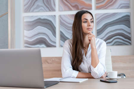 Office manager woman wearing white shirt, sitting to table with laptop and cup of coffee, looking away. Female office worker with brown hair in big light office room. Concept of work