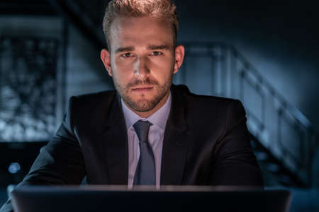 Portrait of tired businessman wearing black suit, working late at night in the office. Office manager working with laptop looking at the camera, blurred background of dark office room